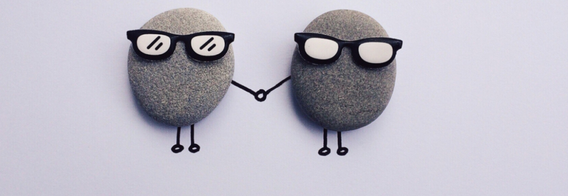 Two small pebbles with legs, arms and sunglasses hold hands