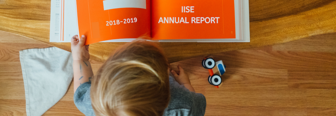 A child turns pages of the IISE annual report