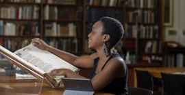 A student looks at an oversized book in a library