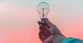 A hand holds a clear light bulb