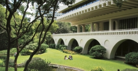 Asian inspired building and gardens with people sitting on the grass