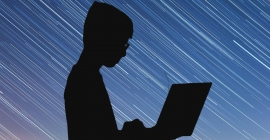 A silhouette of a person using a laptop